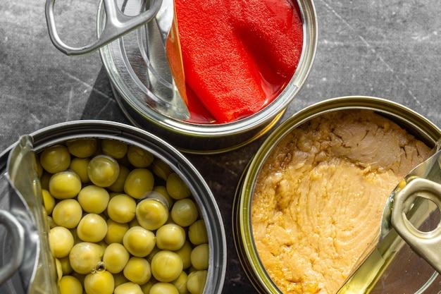 赤唐辛子、明るいマグロ、エンドウ豆の画像の中央に三角形の形で配置された3つの開いたブリキ缶の上からのクローズアップショット、灰色の表面と柔らかな自然光