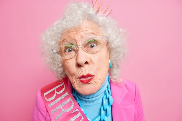 Close up shot of funny curious elderly woman looks with great interest, keeps lips rounded wears bright makeup wears transparent glasses dressed in festive clothes for special occasion