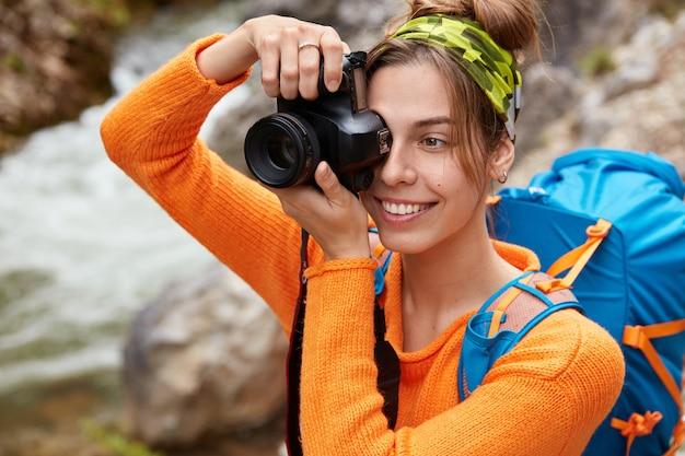 Immagine ravvicinata di felice giovane turista femminile caucasico vestito con un ponticello arancione brillante