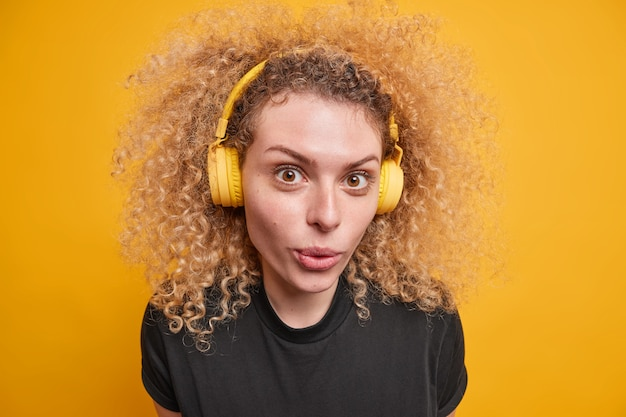 Close up shot of good looking curly teenage girl wears wireless headphones on ears enjoys sound quality listens music keeps lips folded dressed in casual black t shirt isolated over yellow wall