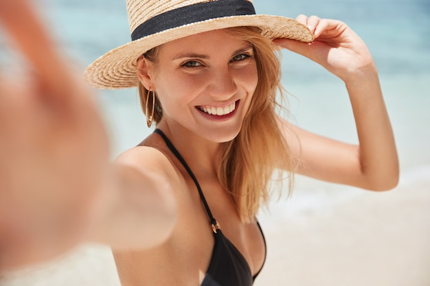 Close up shot of good looking female tourist enjoys free time outdoor near ocean on beach,  during leisure on sunny summer day, poses for selfie.