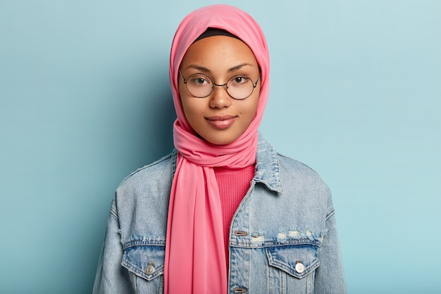 Close up shot of good looking woman with healthy skin, wears transparent glasses, pink scarf on head, jean jacket, isolated over blue wall, has confident gaze. religion concept