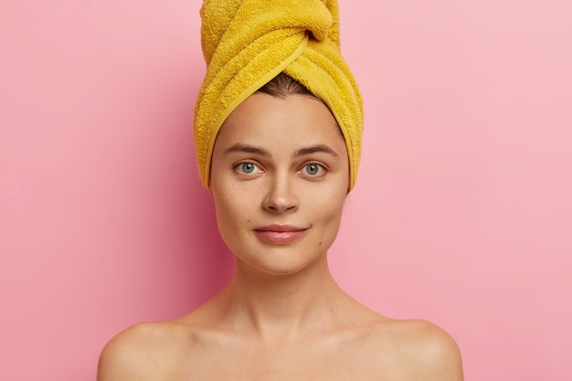 Close up shot of gorgeous fresh european woman with towel on head, has clean face, healthy skin, stands shirtless, takes shower, going to apply makeup, has natural beauty. body care concept.