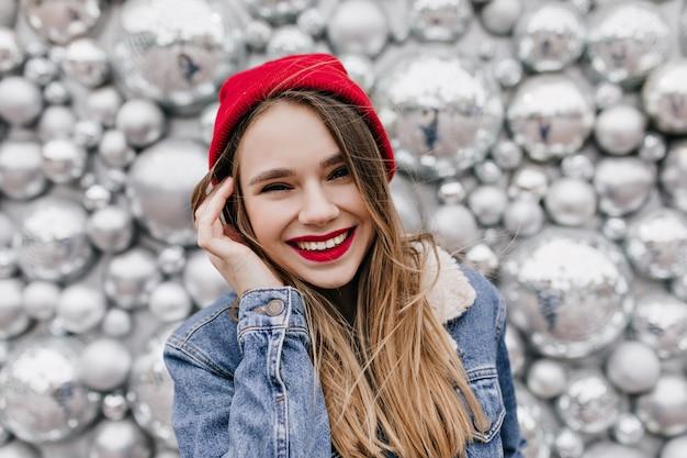 Colpo del primo piano della splendida donna bianca con i capelli lunghi sorridente sulla parete di scintilla in una giornata fredda. ragazza estatica in cappello rosso e giacca di jeans che ride durante il servizio fotografico.