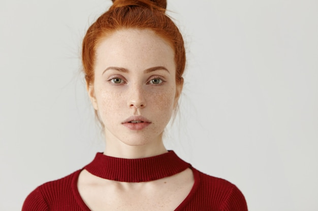 Close up shot of gorgeous young caucasian woman with perfect freckled skin and ginger hair looking with subtle smile, wearing beautiful maroon dress with cut out before going to party