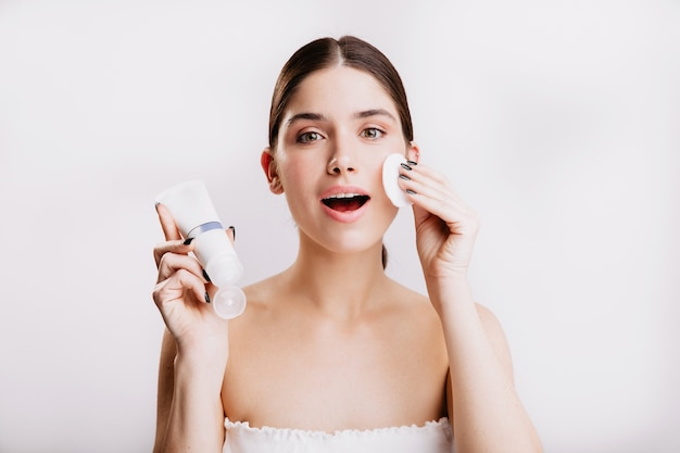 Close-up shot of green-eyed girl doing spa procedure on white wall. woman moistens her face with dove cream.