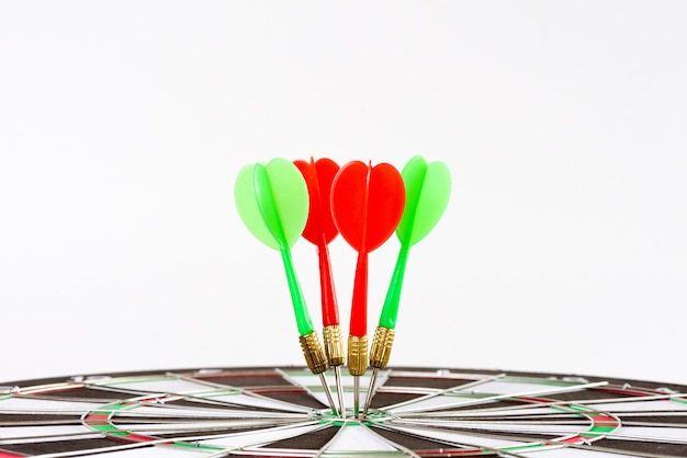 Close up shot green and red darts arrows in the target center.