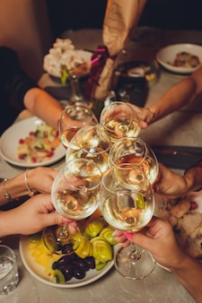 Close up shot of group of people clinking glasses with wine or champagne in front of bokeh