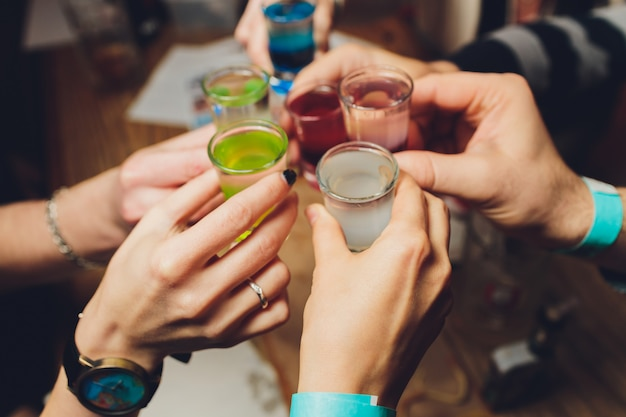 Close up shot of group of people clinking glasses with wine or champagne