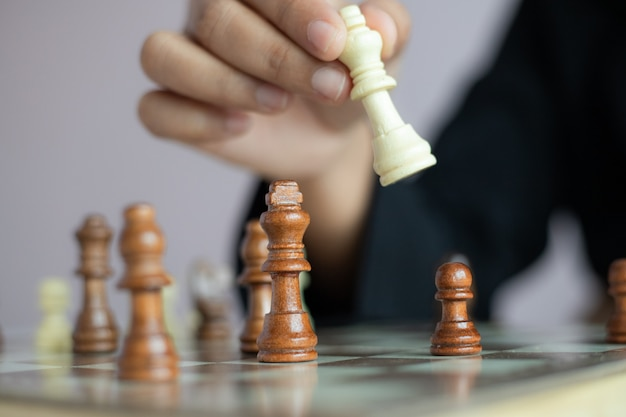 Close up shot hand of business woman playing the chess board to win by killing the king of opponent metaphor business competition winner and loser select focus shallow depth of field