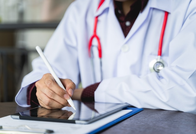 Close up shot hand of doctors with stethoscope are using tablets to write treatment reports or view