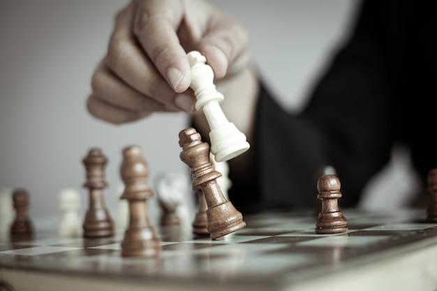 チェス盤を遊んでいるビジネスウーマンのショットの手を閉じる