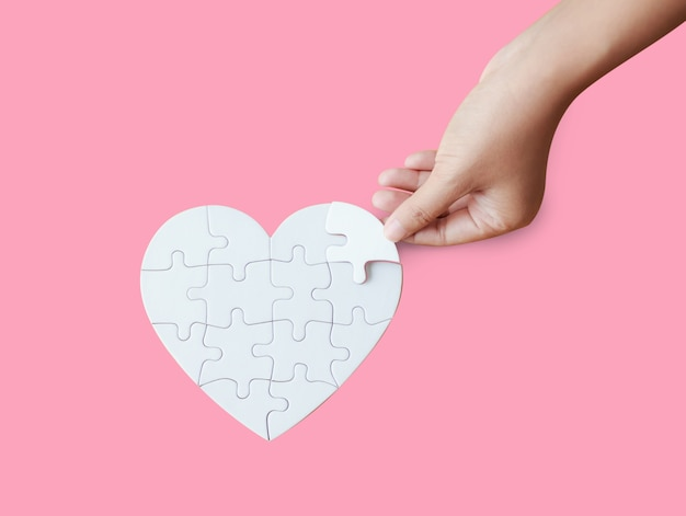 Close up shot hand of woman playing heart shape jigsaw puzzle on pink background