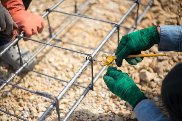 Close up shot on hands fixing steel reinforcement bars with officer