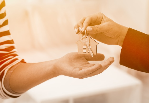 Close up shot of hands giving keys of an apartment.