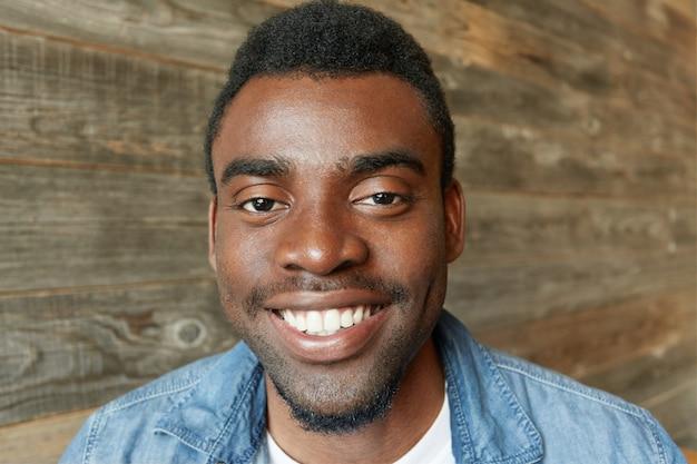 Immagine ravvicinata di bello studente africano con la barba vestita in camicia di jeans che sorride felicemente, mostrando i suoi denti bianchi, con un aspetto gioioso e contento