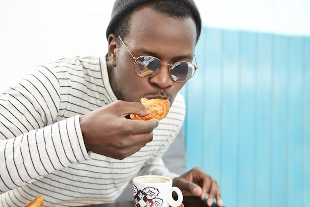 Close up shot of handsome dark-skinned man in hat and round shades eating delicious croissant for breakfast and drinking coffee at cozy cafe in the morning. people, lifestyle, food and nutrition