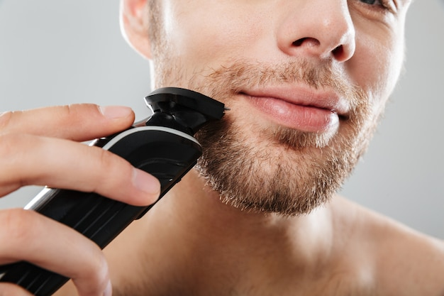 Close up shot of handsome man smiling while shaving his face with electric shaver making morning procedure in bathroom against grey wall