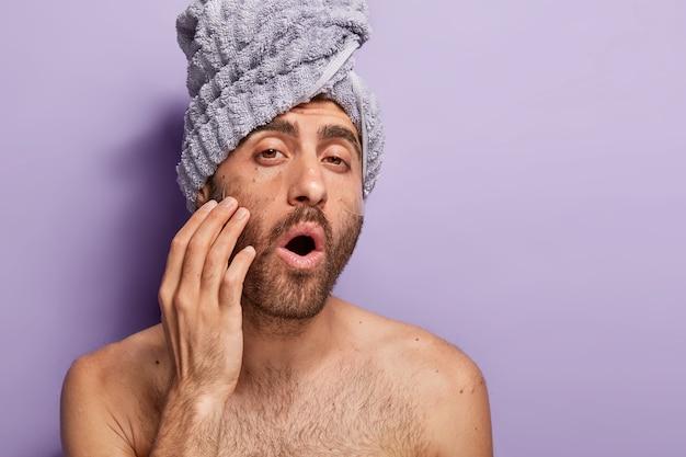 Immagine ravvicinata di bell'uomo con la barba lunga ha maschere sotto gli occhi, guarda la telecamera con la bocca spalancata, ha il corpo nudo, asciugamano avvolto sulla testa