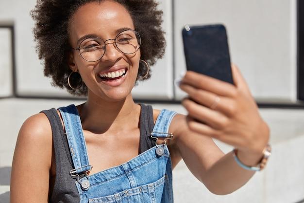 Immagine ravvicinata di felice donna afroamericana tiene il cellulare davanti, sorride ampiamente, scatta un selfie, essendo di buon umore, gode di riposo all'aperto, vestito con abiti estivi alla moda tempo libero