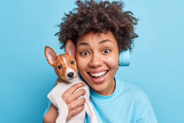 Close up shot of happy afro american woman holds lovely pet near face glad to get pedigree dog as present on birthday have friendly relationships listens music in headphones isolated on blue
