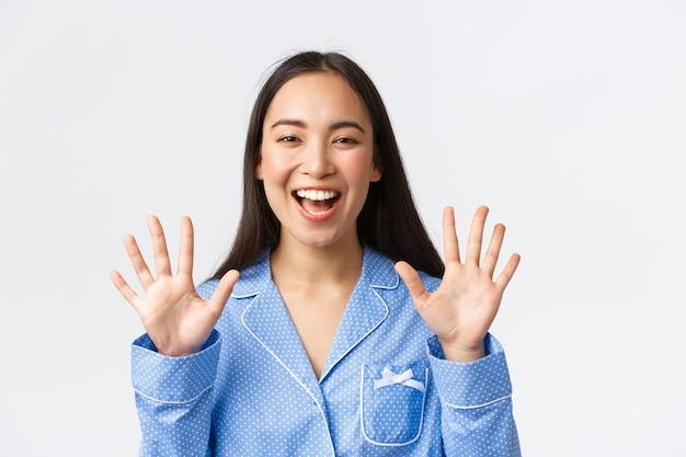 Primo piano di una donna asiatica attraente e felice in pigiama blu che mostra dieci dita e denti bianchi sorridenti, spiega le regole principali o fa ordine, in piedi sfondo bianco, consiglia il prodotto