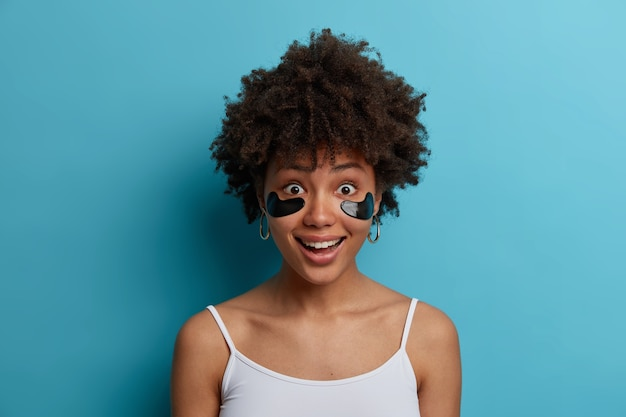Close up shot of happy dark skinned woman has anti aging eye therapy, applies cosmetic patches under eyes, wants to have healthy skin, dressed in casual clothes, isolated over blue wall