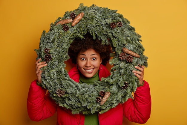 Close up shot of happy dark skinned woman looks through round spruce wreath, dressed in red jacket, makes shot against yellow wall, happy her favourite winter holidays come soon.