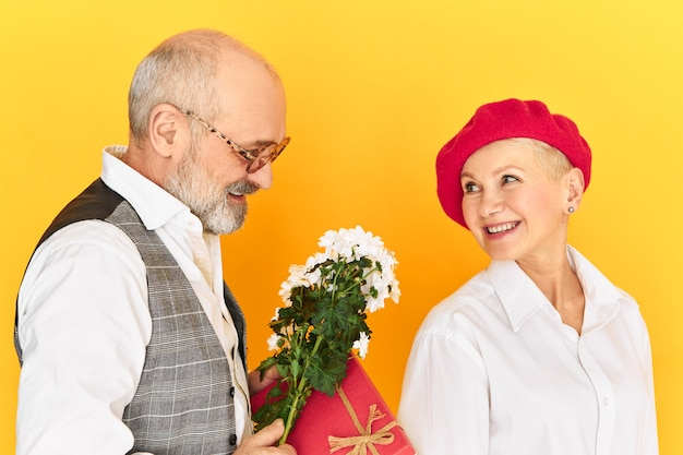 Close up shot of happy elderly couple in stlyish elegant clothes celebrating marriage anniversary, still in love with each other. handsome male pensioner giving flowers to his charming woman
