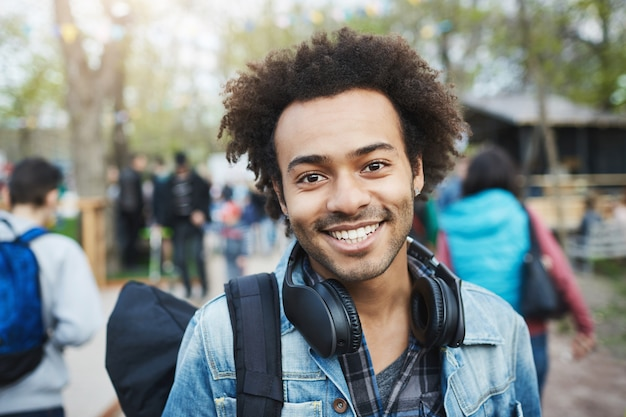 Close-up shot of happy emotive young african-american guy with afro hairstyle and bristle, smiling broadly while wearing denim coat and backpack, walking across park during festival