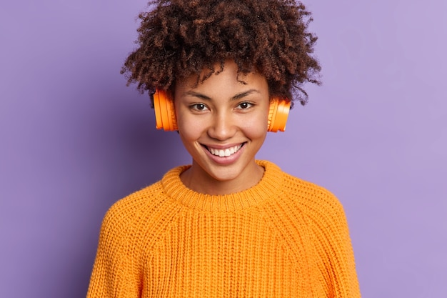 Close up shot of happy female music lover wears wireless stereo headphones on ears enjoys favorite song from playlist smiles positively poses