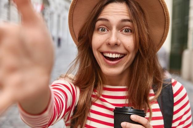 Immagine ravvicinata di felice donna che viaggia ha le mani tese alla fotocamera, fa selfie ritratto