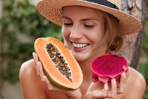 Close up shot of happy female with cheerful expression motivates you eat healthy food, holds papaya and dragon fruit.