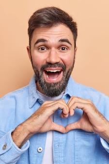 Il primo piano dell'uomo europeo barbuto bello felice mostra il gesto del cuore