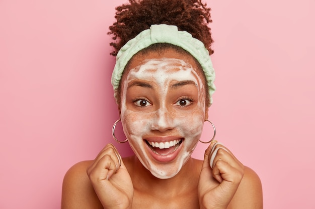 Close up shot of happy impressed curly african american woman raises clenched fists, gets pleasure from hygienic treatments, wears headband on head, washes face with bubble soap, smiles broadly