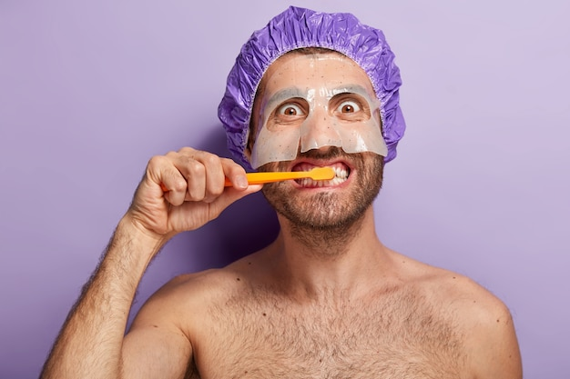 Close up shot of happy man brushes teeth in morning, applies beauty mask, wears shower cap