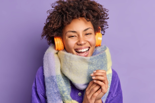 Close up shot of happy young african american woman keeps hands together smiles broadly wears scarf around neck uses wireless headphones for listening music enjoys good sound