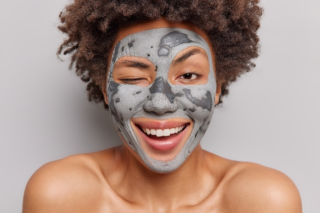 Immagine ravvicinata di una giovane donna afroamericana felice che strizza l'occhio, sorride e gode ampiamente delle procedure per la cura della pelle