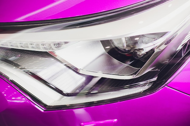 Close up shot headlight in luxury pink car. modern and expensive sport car concept