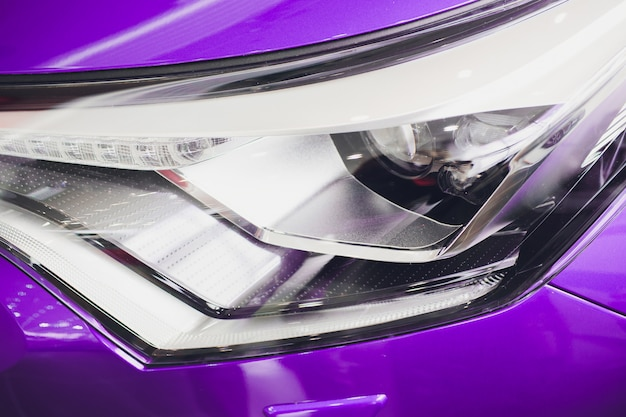 Close up shot headlight in luxury purple car. modern and expensive sport car concept