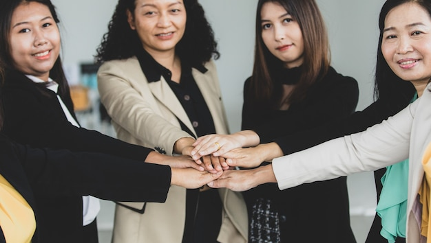 Close up shot of holding hands of middle aged successful confident female businesswoman colleagues group standing smiling together in formal business suit encourage empower commitment partnership.