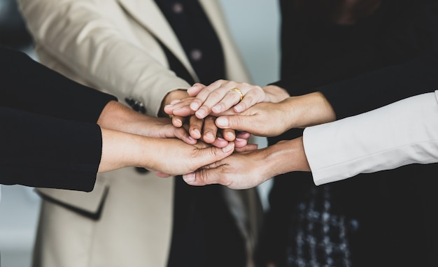 Close up shot of holding hands of unidentified unrecognizable successful female businesswoman group together in formal business suit wears empower encourage as trust teamwork partnership agreement.