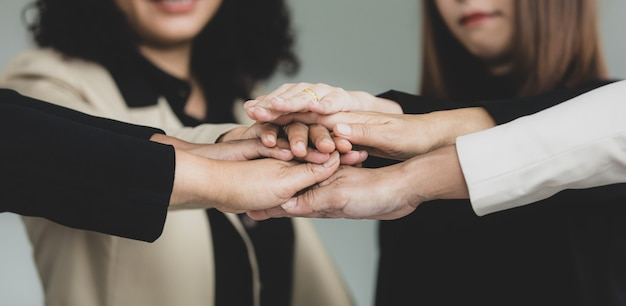 Close up shot of holding hands of unidentified unrecognizable successful female businesswoman group together in formal business suit above working desk with graph chart diagram paperwork document.