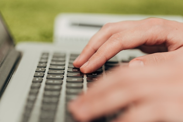 Close-up shot of human hands placed over laptop.