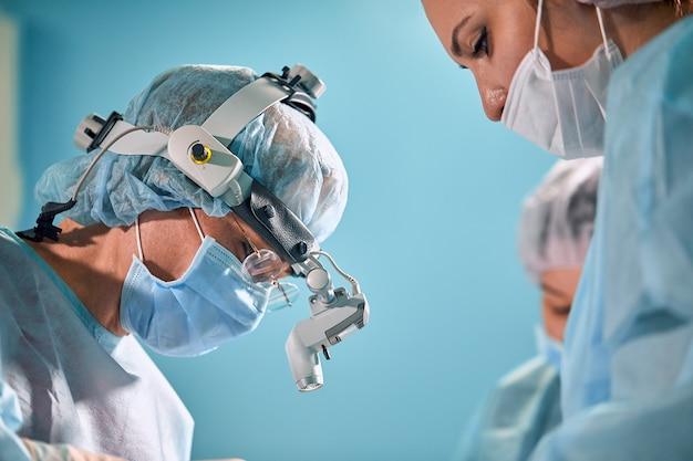 Крупным планом в операционной, ассистент раздает инструменты хирургам во время операции. хирургия в прогрессе. профессиональные врачи, выполняющие операции.