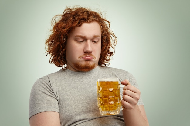 Close up shot of indecisive male with ginger hair holding glass of beer in his hands