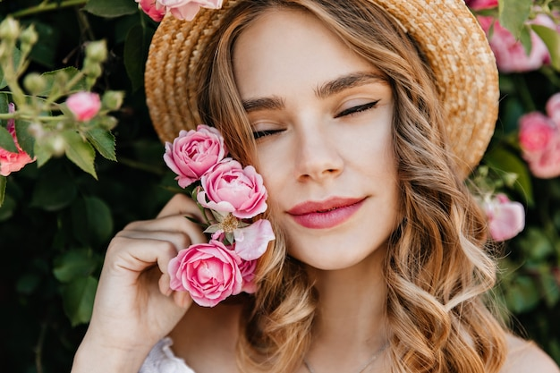 Close-up shot of inspired caucasian woman holding pink flower. outdoor portrait of refined blonde lady chilling in garden.