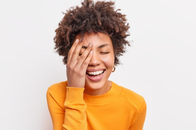 Close up shot of joyful carefree young woman with curly afro hair smiles toothily keeps eyes closed makes face palm wears orange jumper expresses happiness isolated over white  wall