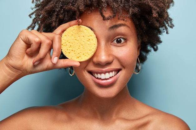 Close up shot of joyful woman with dark healthy skin, holds sponge on eye, has cosmetic procedures, poses half naked over blue wall. smiling female has natural beauty, removes make up.