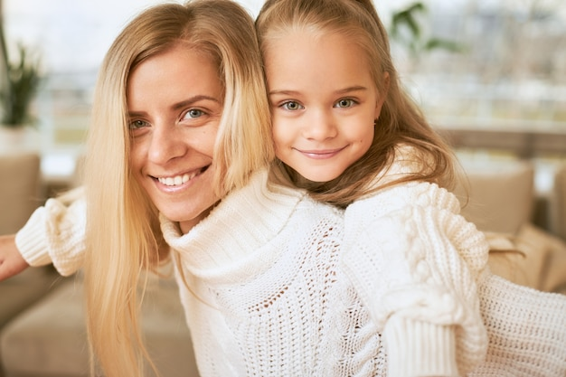 Close up shot of joyful young blonde female in white sweater giving back ride yo her adorable baby daughter spending winter december day at home, laughing, bonding and entertaining themselves